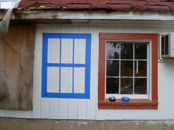 """Shape of proposed windows in blue masking tape. Primo said, """"why not just put tape on the walls? We can have photos of you, Pollo and me looking out. Much cheaper."""""""