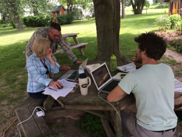 (from left) Growing Manager Chris Voss, Organic Crop Inspector Mary Wilson, and Fertility Manager Andrew Stewart review 2013 Angelic Organics organic growing records and 2014 projections.