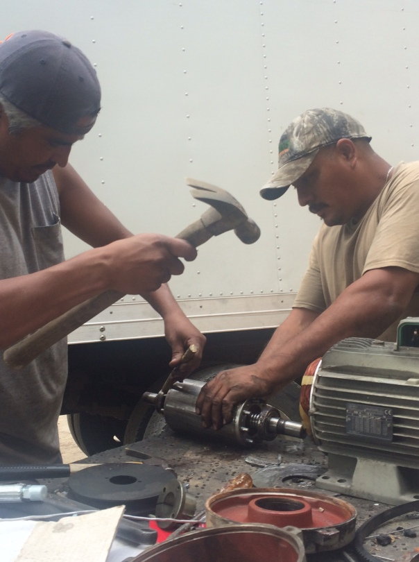 Primo and Pollo repair the motor on our delivery truck's refrigeration unit
